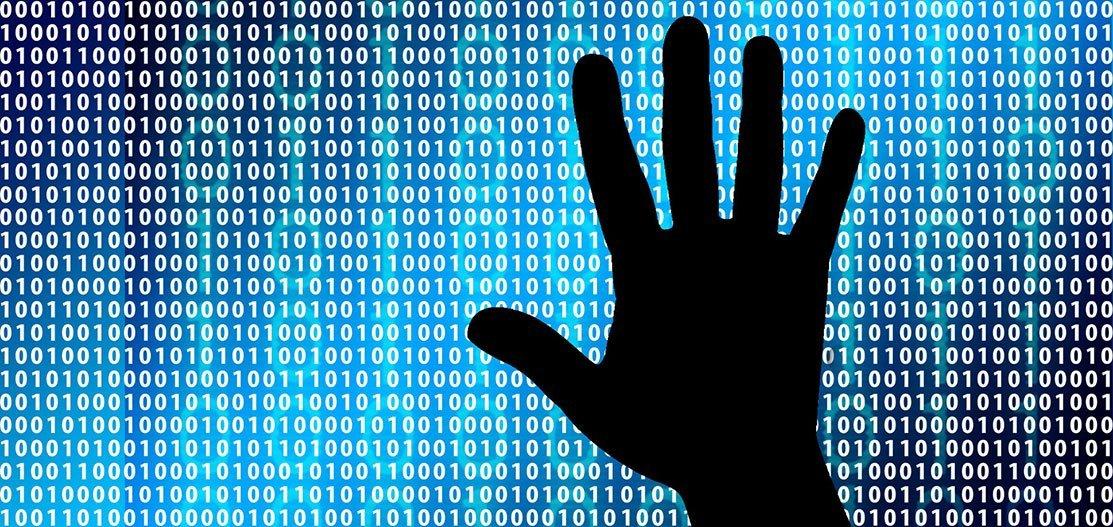 Eine Hand vor der Zahlenkombinationen aus Nullen und Einsen.